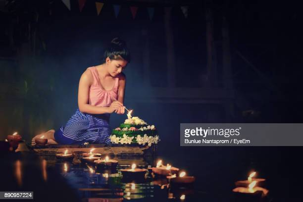 young woman burning incense sticks by diyas floating on pond - diya oil lamp stock pictures, royalty-free photos & images