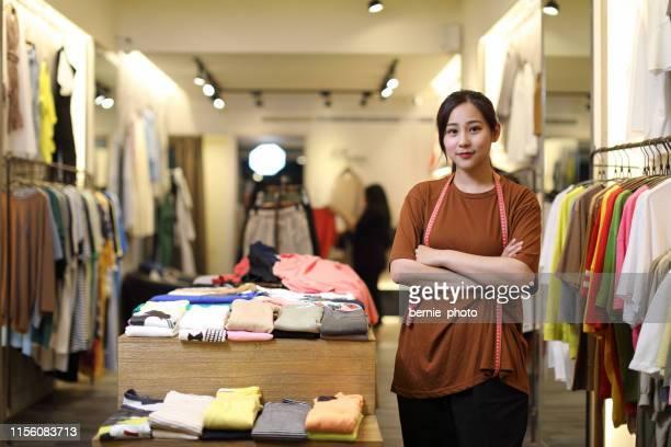 proprietário do negócio da mulher nova em uma loja de roupa, retrato - pequeno - fotografias e filmes do acervo