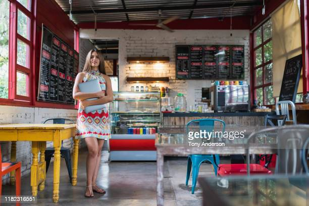 Young woman business owner with laptop standing in her coffee shop
