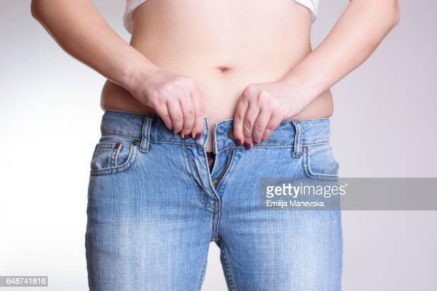 young woman buttoning tight jeans - dieting concept - too small stock pictures, royalty-free photos & images
