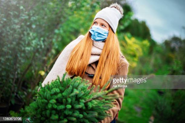 young woman buying a christmas tree. - christmas tree farm stock pictures, royalty-free photos & images