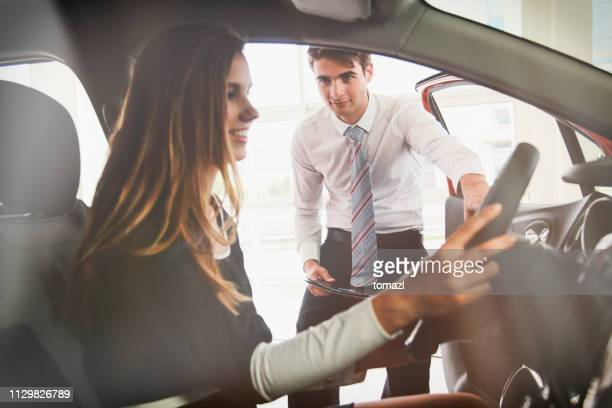 young woman buying a new car - buying a car stock pictures, royalty-free photos & images