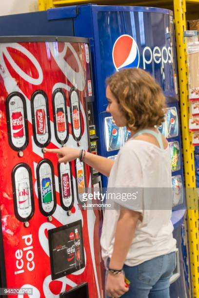 Young woman buying a soda can at a vending machine
