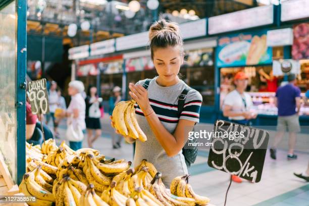 young woman buying bananas at the market - local produce stock pictures, royalty-free photos & images