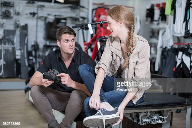 Young woman buying bicycle shoes, salesman advising