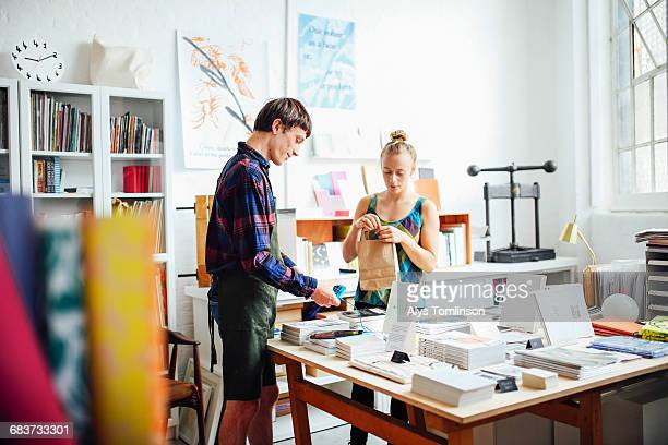 young woman buying book from young craftsman in art bookshop - book store stock photos and pictures