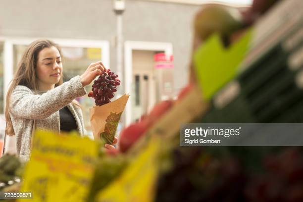 young woman buying bunch of grapes from market stall - sigrid gombert stockfoto's en -beelden
