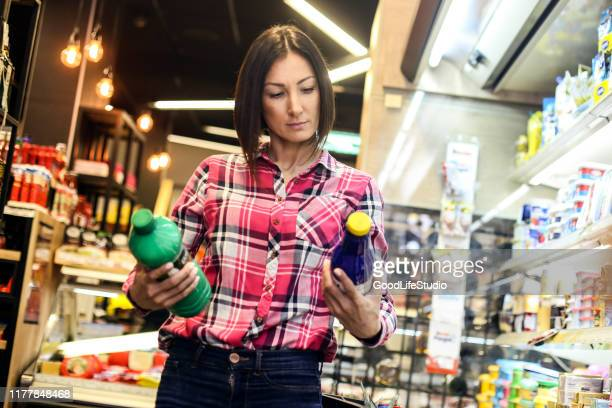 giovane donna che acquista latticini - confronto foto e immagini stock