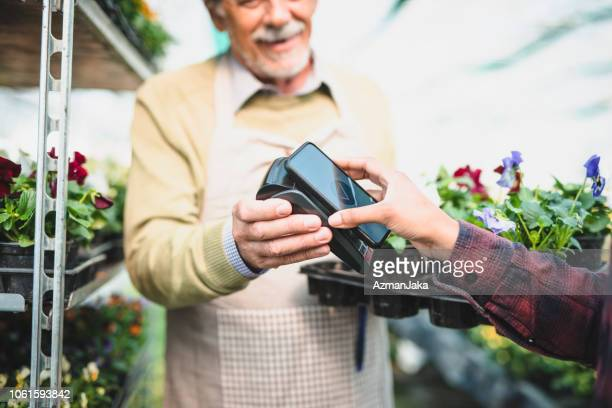 Young woman buying flowers and paying with her smart phone