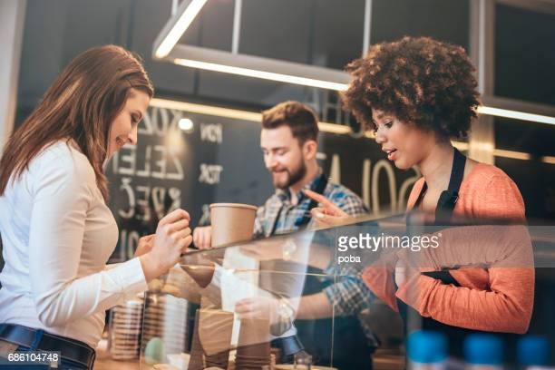 Young woman buying   food  at snack bar