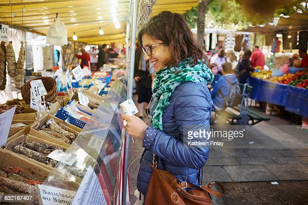 Young woman buying fresh food at market stall