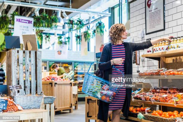 Young woman buying fruit juice while carrying basket at supermarket