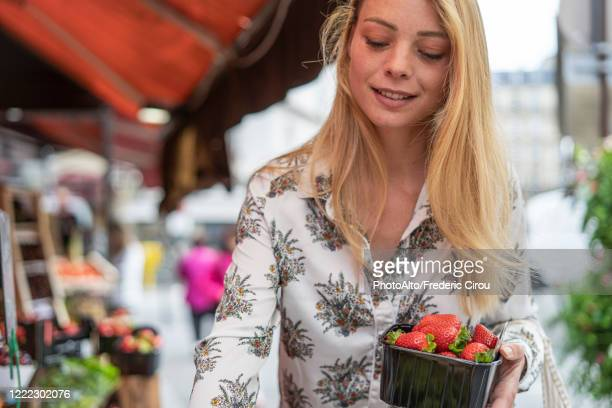 young woman buying fruits at market stall - regarder vers le bas photos et images de collection