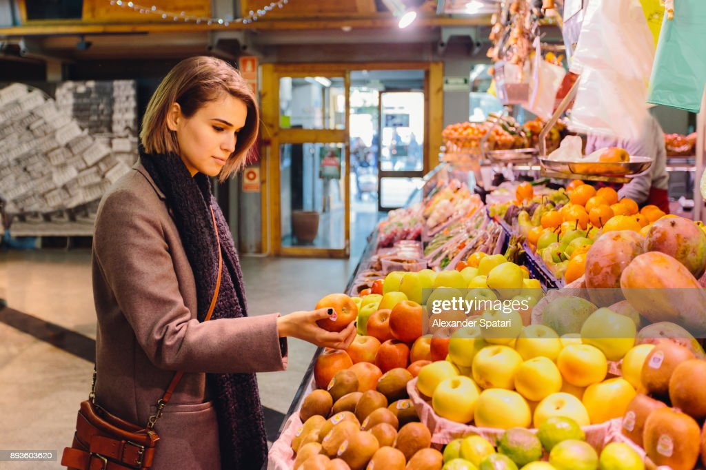 Young woman buying fruits at the farmer's market : Stock Photo