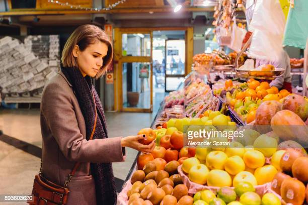 Young woman buying fruits at the farmer's market