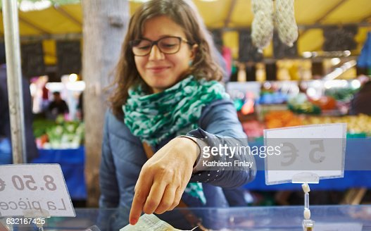 Young woman buying goods at market stall