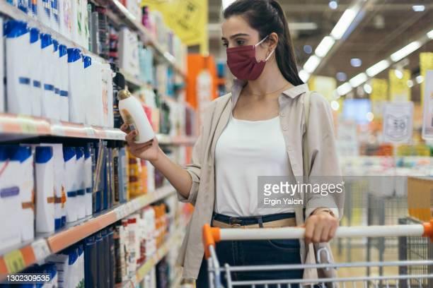 jonge vrouw die kruidenier in supermarkt koopt - shampoo stockfoto's en -beelden