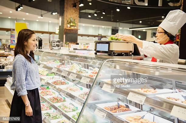 若い女性食料品のスーパーで購入