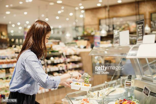 young woman buying grocery in supermarket - delicatessen stock pictures, royalty-free photos & images