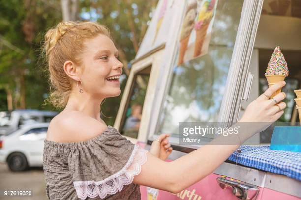 young woman buying ice cream from food truck - ice cream parlor stock photos and pictures