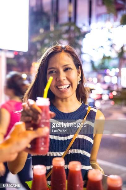 Young woman buying iced fruit juice in Bangkok at night