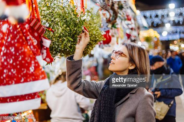 young woman buying mistletoe at the christmas market - gui photos et images de collection