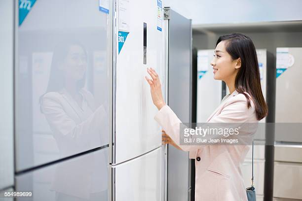 Young woman buying refrigerator in electronics store