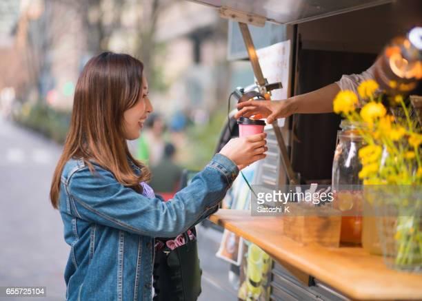 若い女性のスタンド ショップでソフトド リンクを購入 - ショッピングエリア ストックフォトと画像