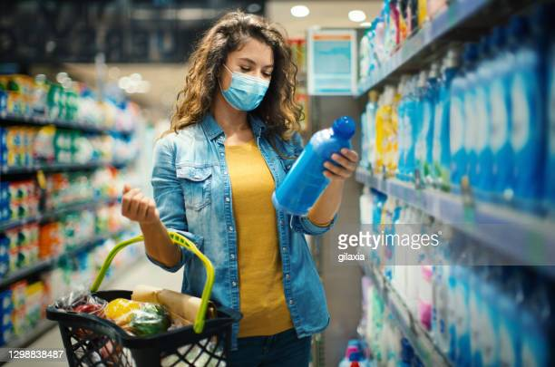 young woman buying some food at a reopened supermarket. - cleaning agent stock pictures, royalty-free photos & images