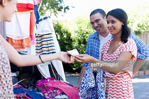 Young woman buying sundress on market stall