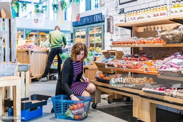 Young woman buying tomatoes while crouching in supermarket