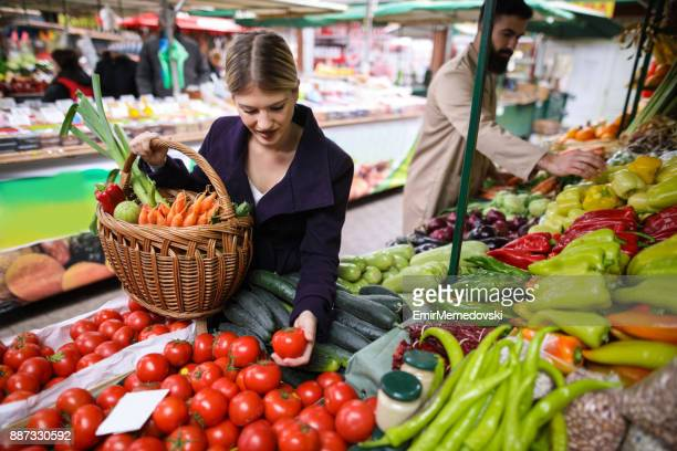 Young woman buying vegetables at farmer's market stall.