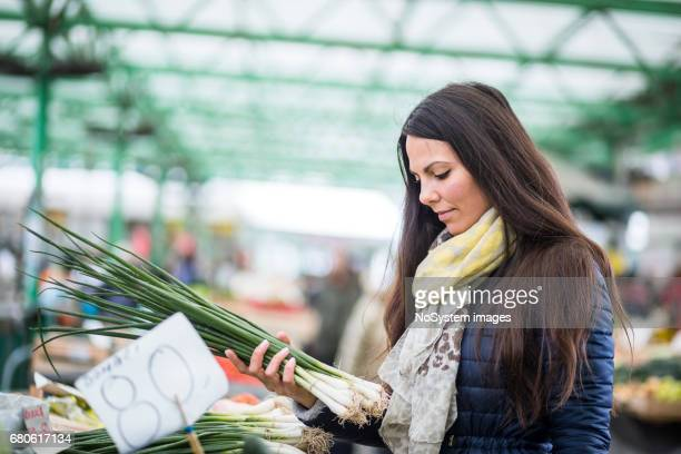 Young woman buying vegetables at the market place