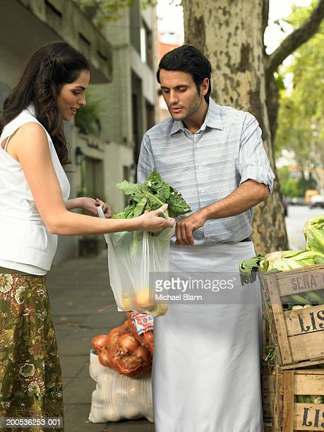 Young woman buying vegetables from market trader