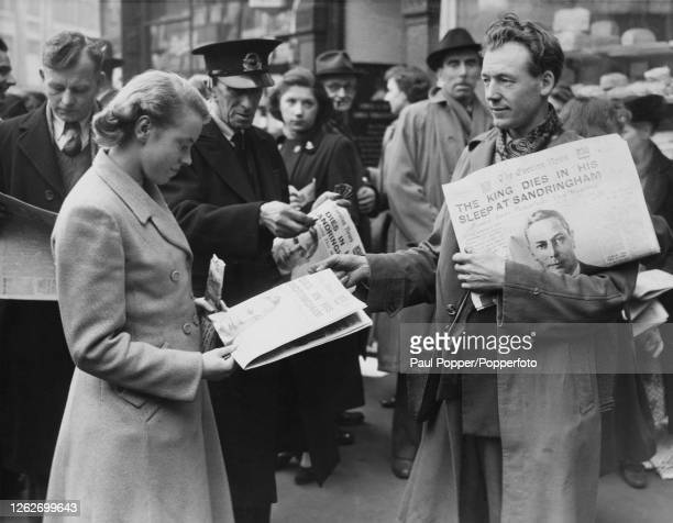 A young woman buys a copy of the Evening News from a newspaper vendor and reads the headline 'The King Dies in his Sleep at Sandringham' following...