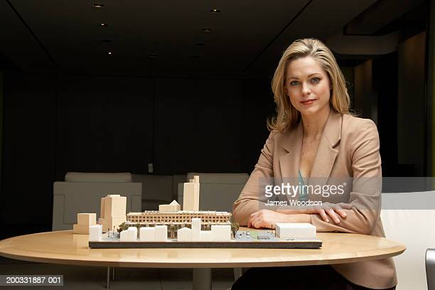 Young woman by architectural model on table, portrait