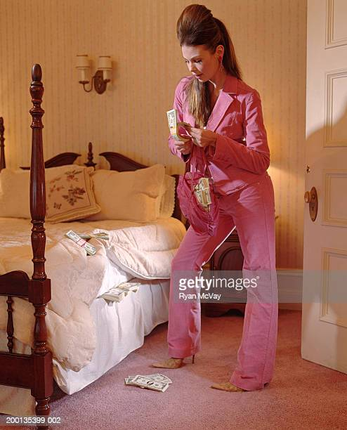 Young woman by bed fanning wad of money