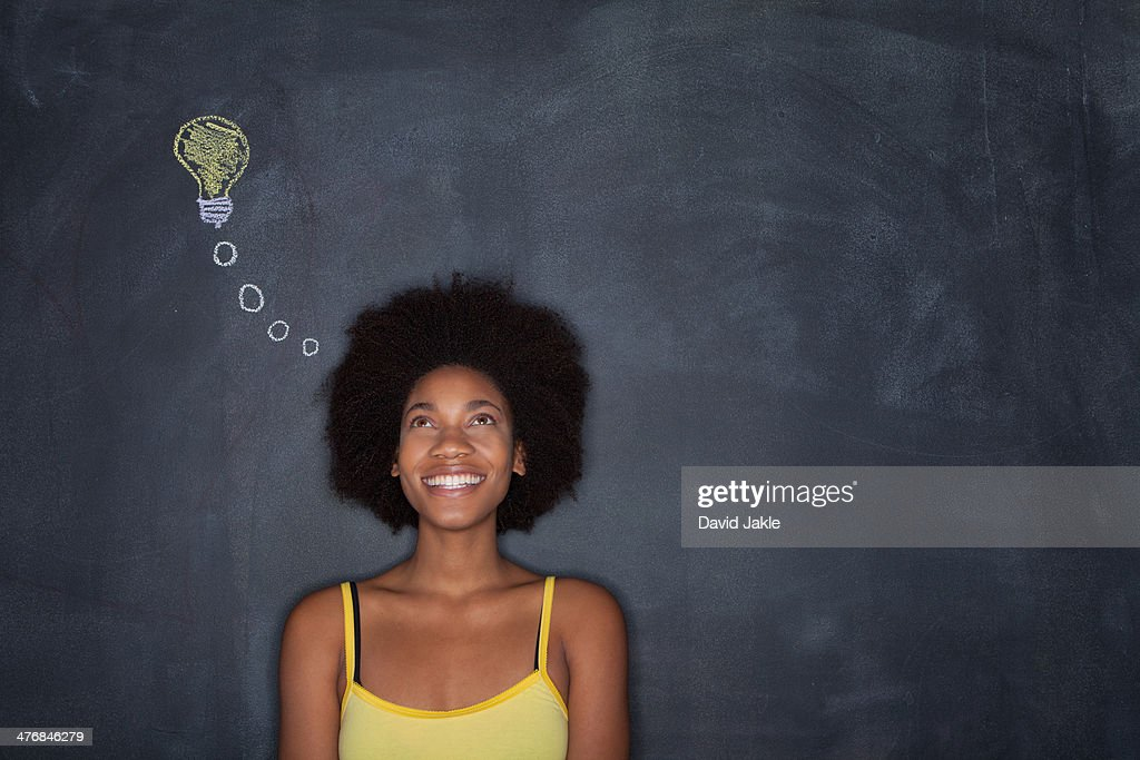 Young woman by blackboard with lightbulb : Stock Photo