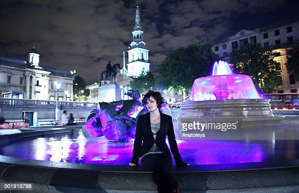Young woman by fountain at night