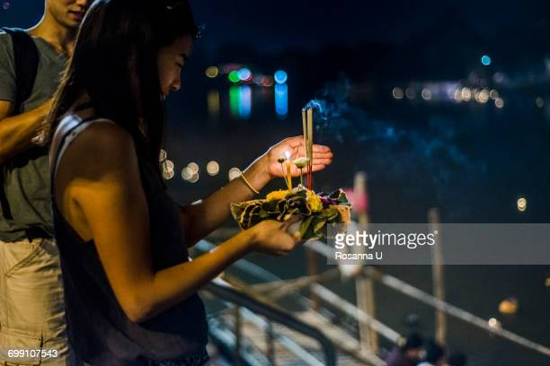 """""""young woman by ping river in chiang mai during loy krathong lantern festival, releasing floating lantern down the ping river, chiang mai, thailand"""" - loi krathong stock photos and pictures"""