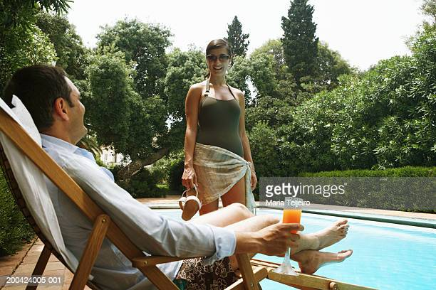 Young woman by pool smiling at man relaxing in sun lounger