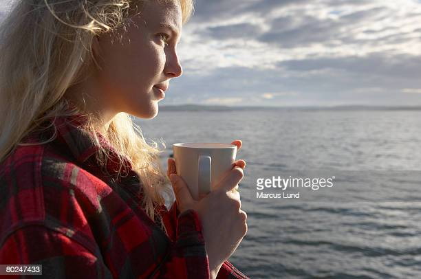 Young Woman By sea with mug of tea.