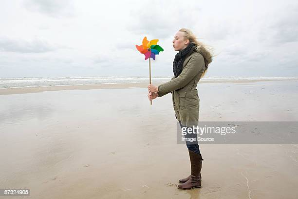 young woman by sea with pinwheel - paper windmill stock photos and pictures