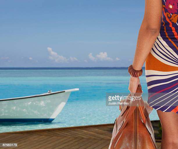 Young woman by sea with suitcase, rear view