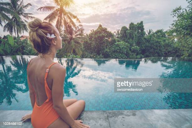 young woman by the edge of an infinity pool, ubud, bali enjoying tropical climate vacations in asia - swimwear stock pictures, royalty-free photos & images