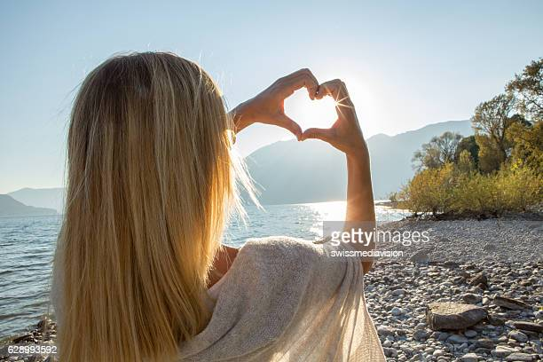 Young woman by the lake framing sunrise in heart shape