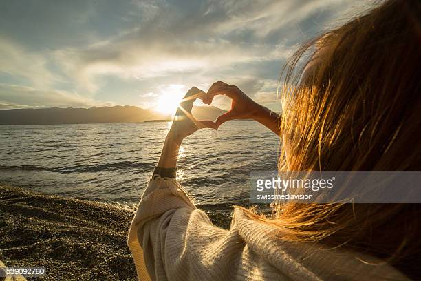 young woman by the lake making heart shape finger frame - beauty in nature stock pictures, royalty-free photos & images