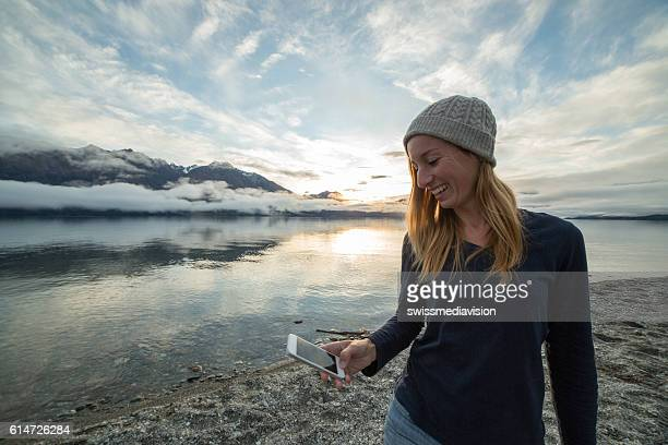 Young woman by the lake uses smart phone