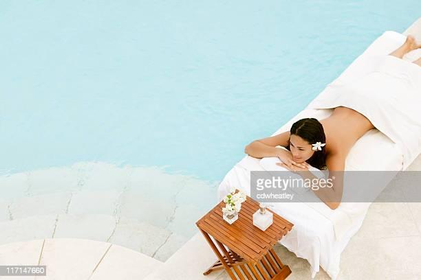 Jeune femme près de la piscine dans un centre de villégiature de luxe avec spa