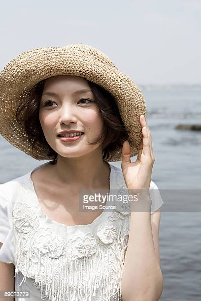 young woman by the sea - 麦わら帽子 ストックフォトと画像